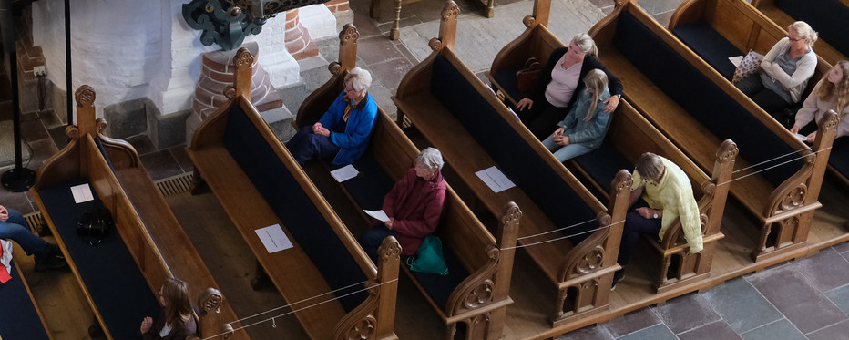 Billede fra Domkirken af bænke med kirkegængere med corona-afstand