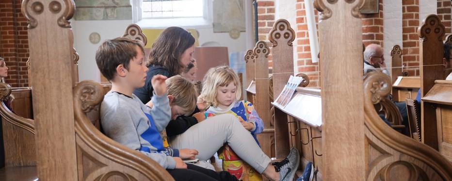 Foto af familie på kirkebænk i Domkirken