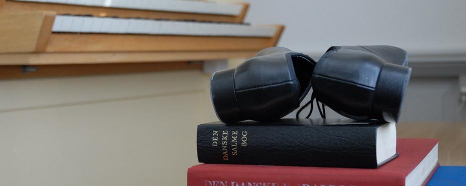 Billede af salmebøger med orgelsko ovenpå. I baggrunden et orgel